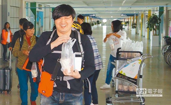 高雄市觀光局贈送珍珠奶茶,韓國遊客笑呵呵。(柯宗緯翻攝)