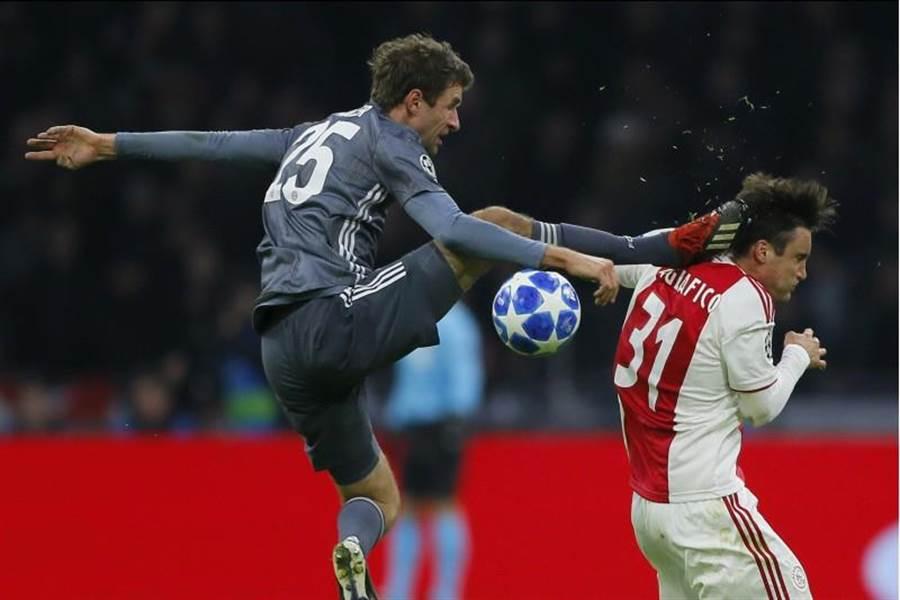 拜仁慕尼黑球星穆勒(左)搶球時一腳踹在阿賈克斯左後衛塔利亞菲柯的頭,立刻遭到紅牌罰下。(美聯社)
