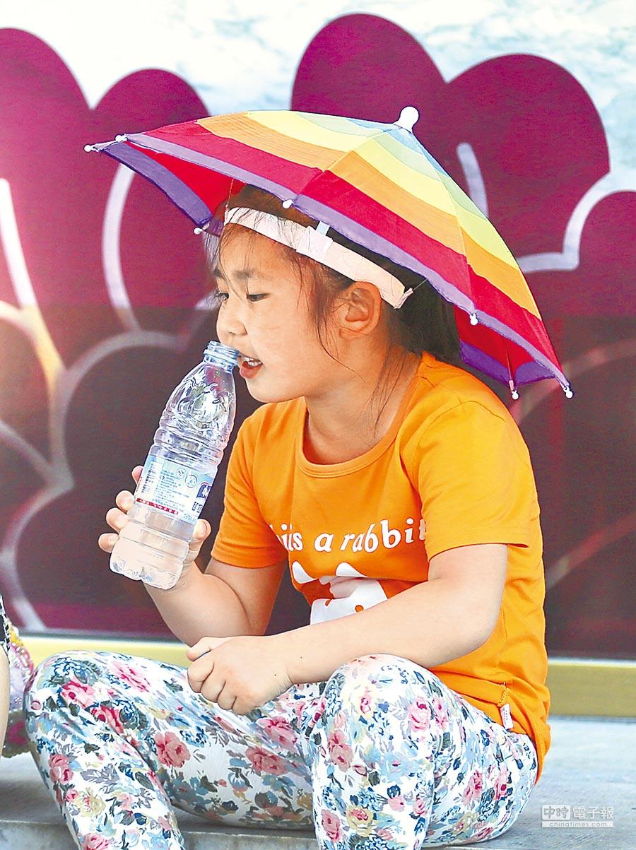 一名頭戴遮陽傘的孩童在街邊喝水。(中新社資料照片)
