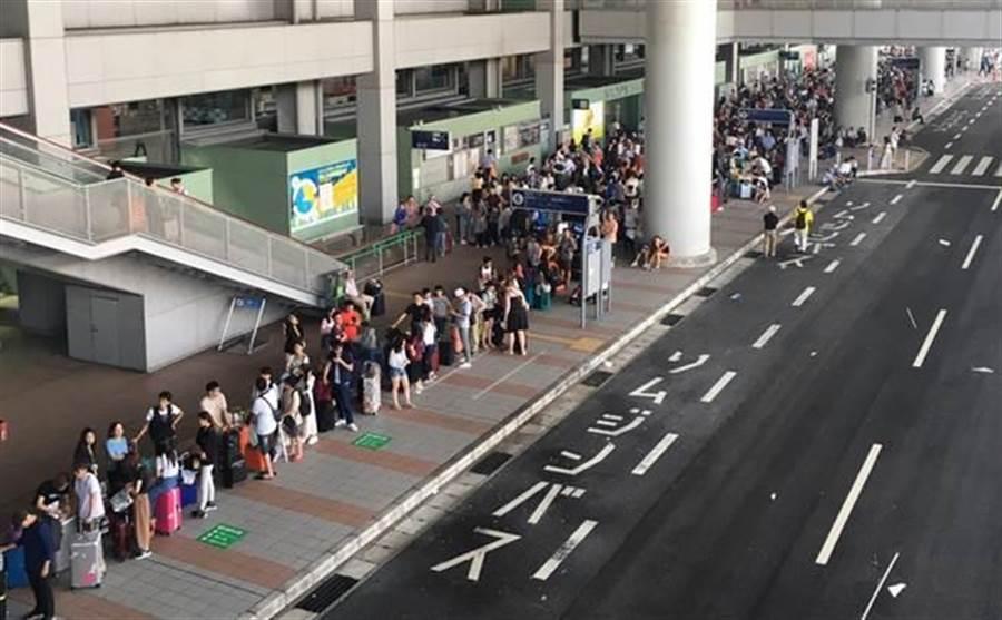 強颱燕子9月4日襲日本,關西國際機場淹水癱瘓,大量旅客滯留,5日有許多旅客排隊等著搭巴士離開機場。(許姓民眾提供/中央社)