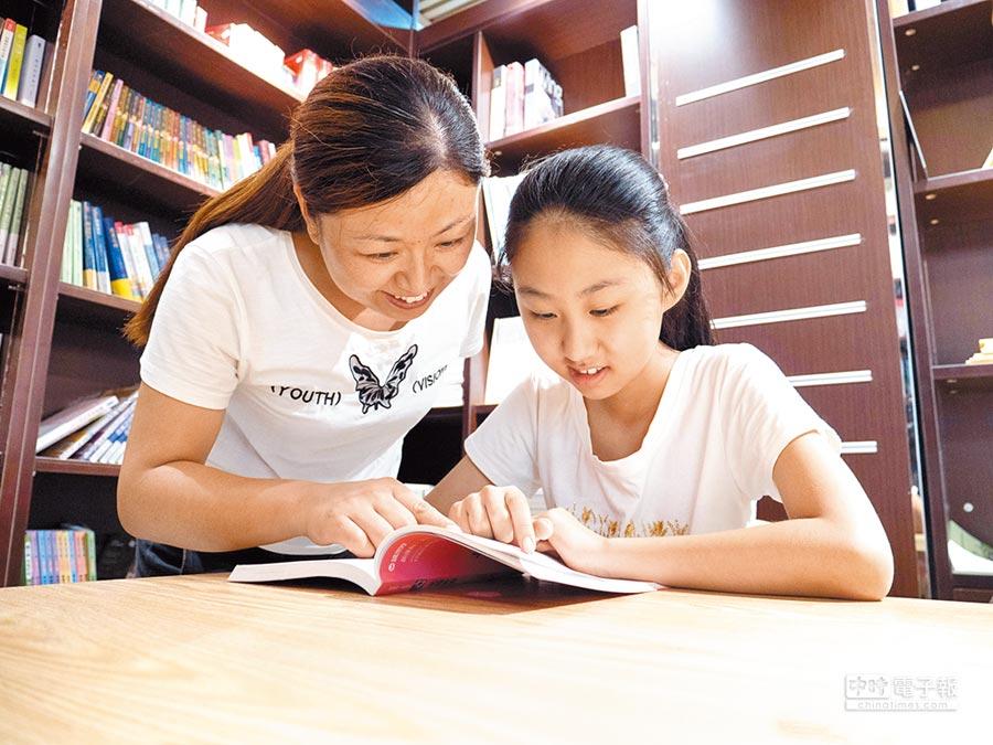 7月22日,小朋友在家長的陪伴下閱讀。(新華社)