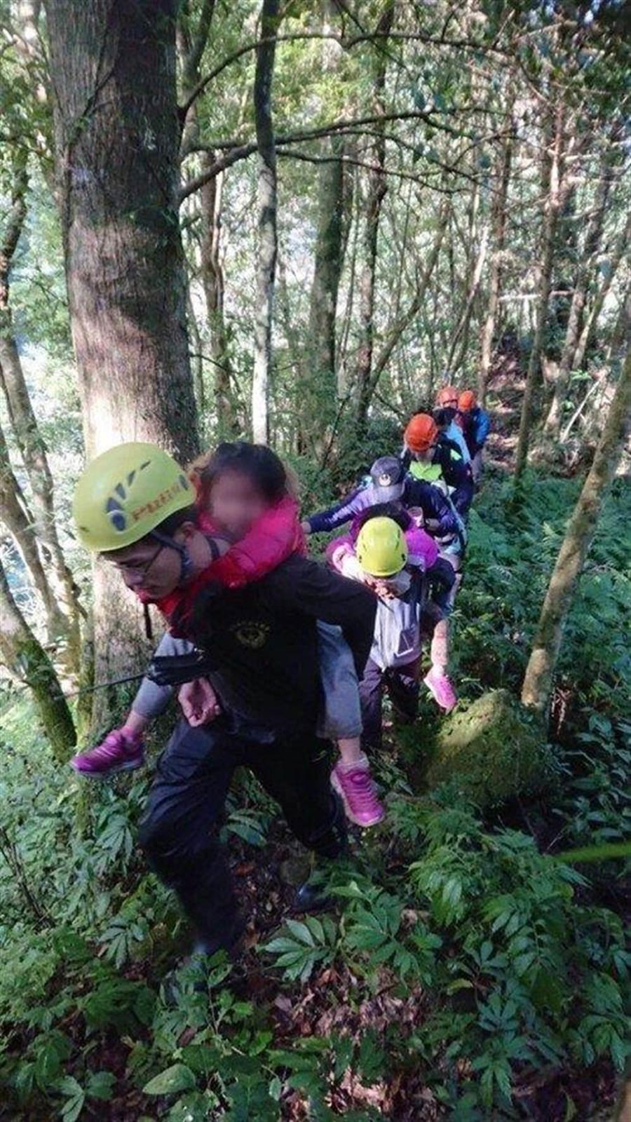 搜救人員背幼童下山。(圖/消防局提供)