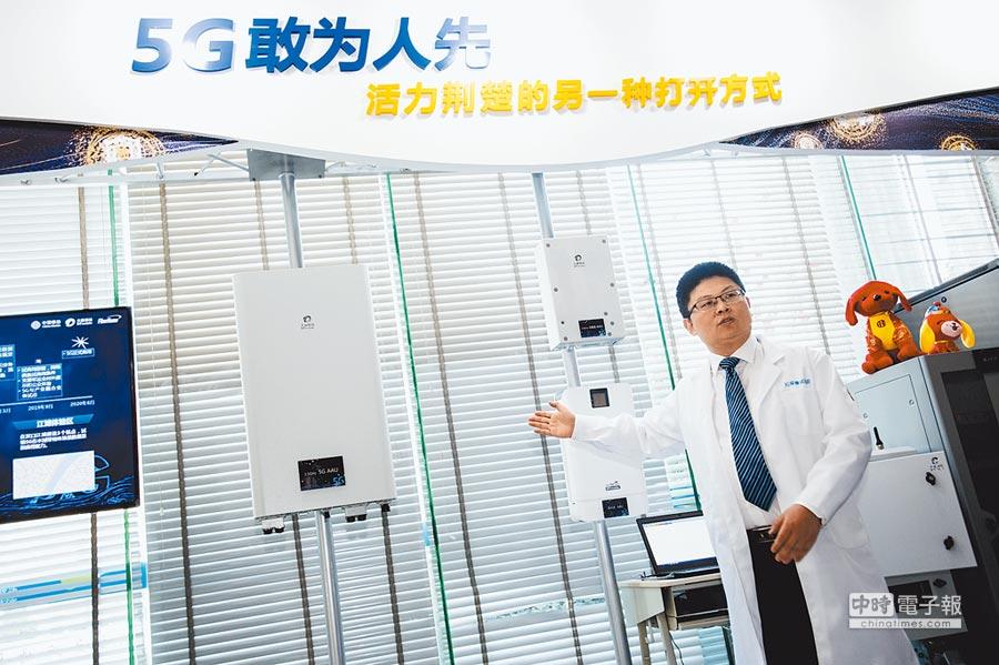 2月1日,湖北首個室外5G試驗基地台在武漢開通,工作人員介紹5G試驗基地台的射頻單元。(新華社)
