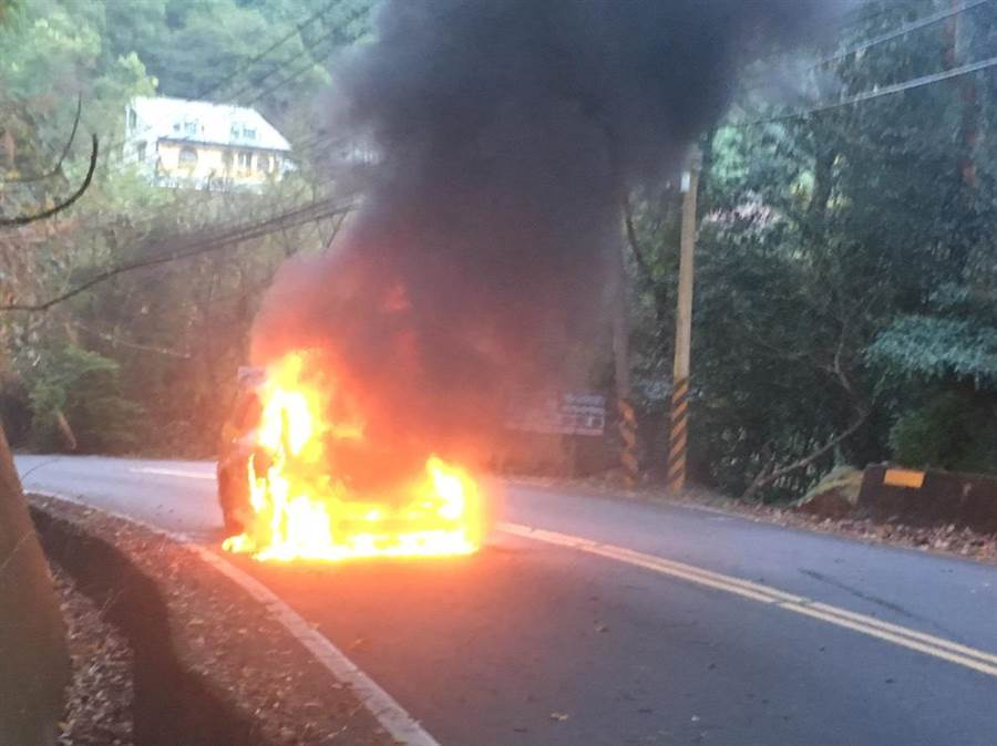 計程車行經仙山上坡路段冒出黑煙,熊熊火勢淹沒車體。(巫靜婷翻攝)