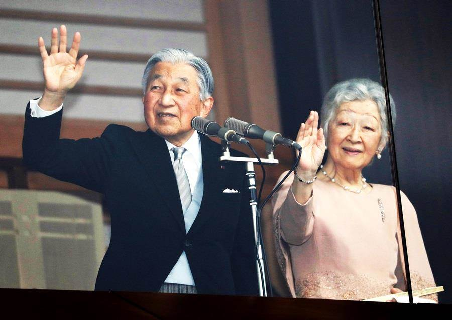 日皇明仁(左)今天歡度85歲生日,他與美智子皇后(右)在皇宮前向大批聚集民眾揮手致意。(圖/路透社)