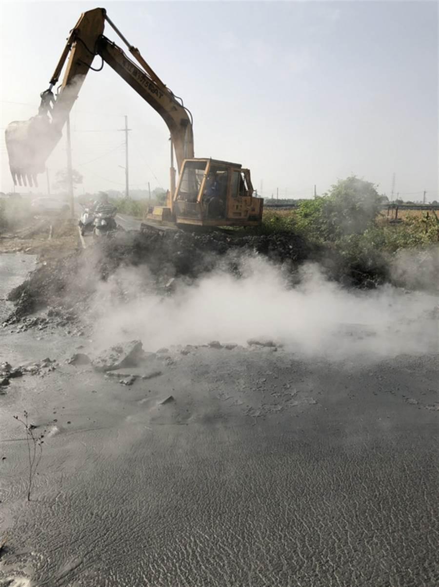 屏東萬丹泥火山去年12月24日上午8時許噴發,噴發地點在萬丹鄉灣內村一條產業道路上,造成道路毀損,鄉公所雇用怪手清除泥漿。中央社記者郭芷瑄攝  107年12月24日