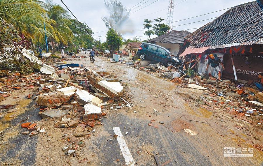 印尼爪哇萬丹省卡里塔(Carita)的居民23日重返海嘯肆虐後的家園,滿目瘡痍的景象讓他們欲哭無淚。遠處還可以看見位於巽他海峽的「喀拉喀托之子」仍然持續冒出火山灰。(法新社)