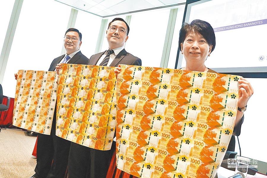 香港印鈔有限公司阮志才(左)、金管局鮑克運(中)和陳葉小明(右)展示三間發鈔行新「金牛」。