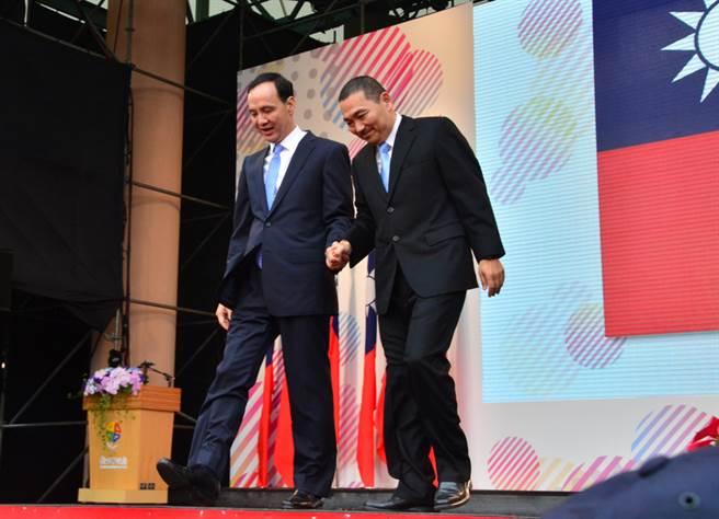 新北市長侯友宜(右)25日正式就職,卸任市長朱立倫(左)牽起他的手,一同走下交接典禮會場台階,也宣布開始邁向角逐總統選舉黨內提名之路。中央社記者黃旭昇新北市攝 107年12月25日