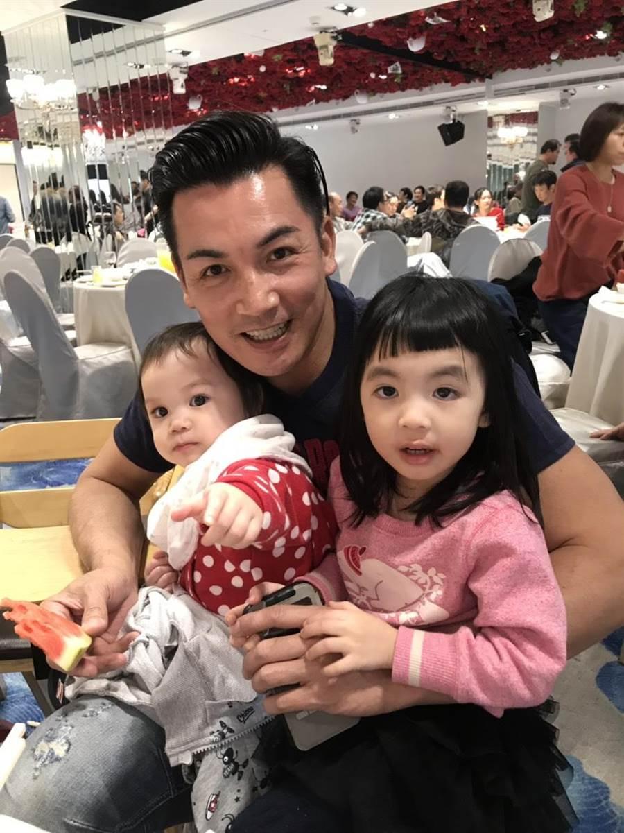 伊正抱兩個女兒步步、靚靚。(林淑娟攝)