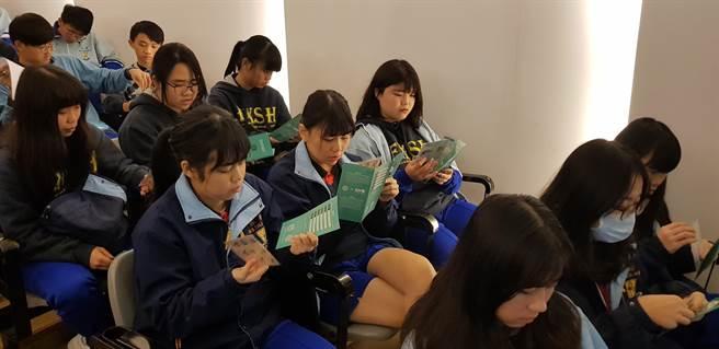 振聲高中學生翻閱「瓩設計獎」簡章與第18屆得獎作品明信片。(戴有良攝)