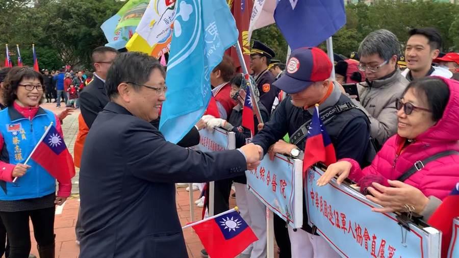 新縣長楊文科(左)主持升旗典禮前與民眾握手致意。(邱立雅攝)