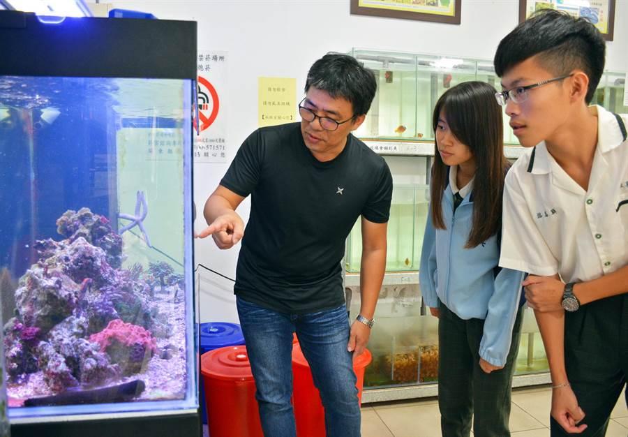 歐武雄(左)將自己對海底生物的喜愛帶進學校,跟著學生一起觀察海底世界。(林和生攝)