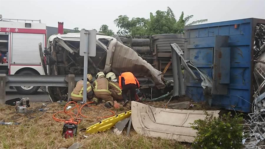 一輛拖板車2日上午在安定交流道閘道自撞翻覆,消防隊到場搶救受困蔡姓駕駛。(李其樺翻攝)