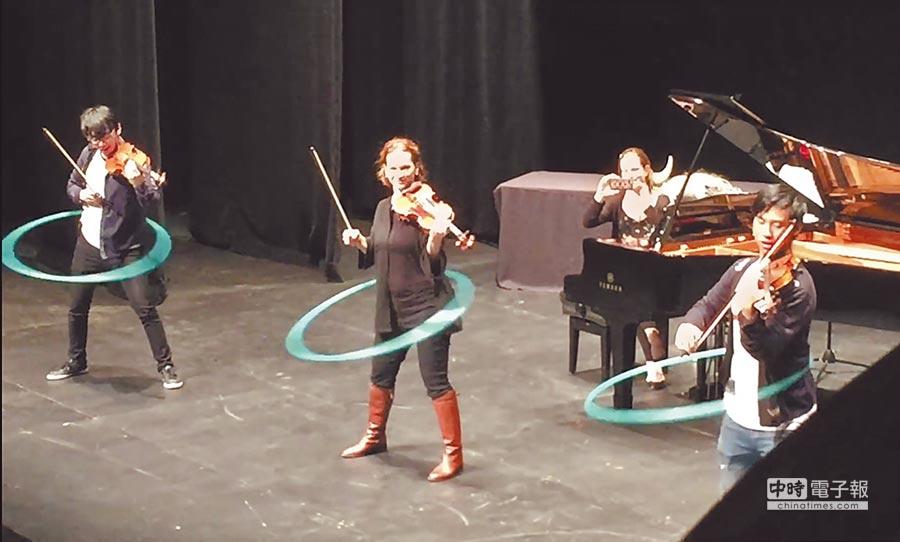 雙琴俠(TwoSet Violin)說服女小提琴家希拉蕊韓(中)一起挑戰邊搖呼拉圈邊演奏小提琴,也讓音樂會現場氣氛飆到最高點。(摘自TwoSet Violin影片)