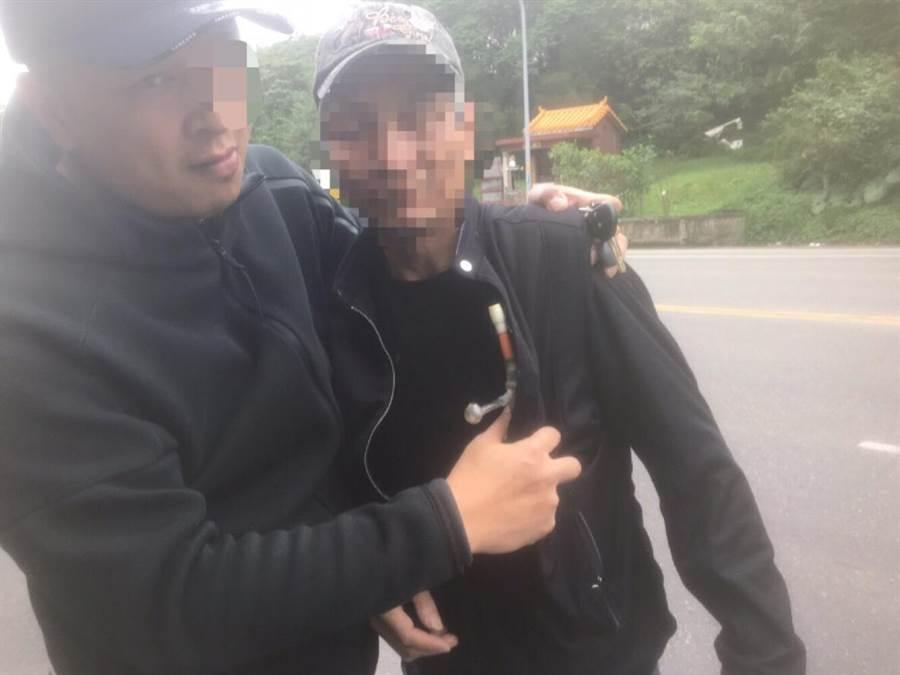 員警逮到吳男和懷裡的安非他命吸食器。(警方提供)