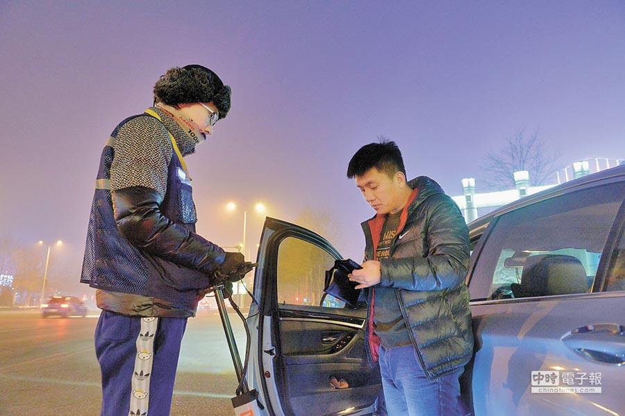 大陸代駕行業興起,年產值破百億人民幣。圖為銀川代駕司機(左)接送顧客。(新華社資料照片)