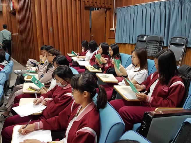 學生認真詳讀及討論瓩設計獎競賽辦法DM(黃珈綺攝)