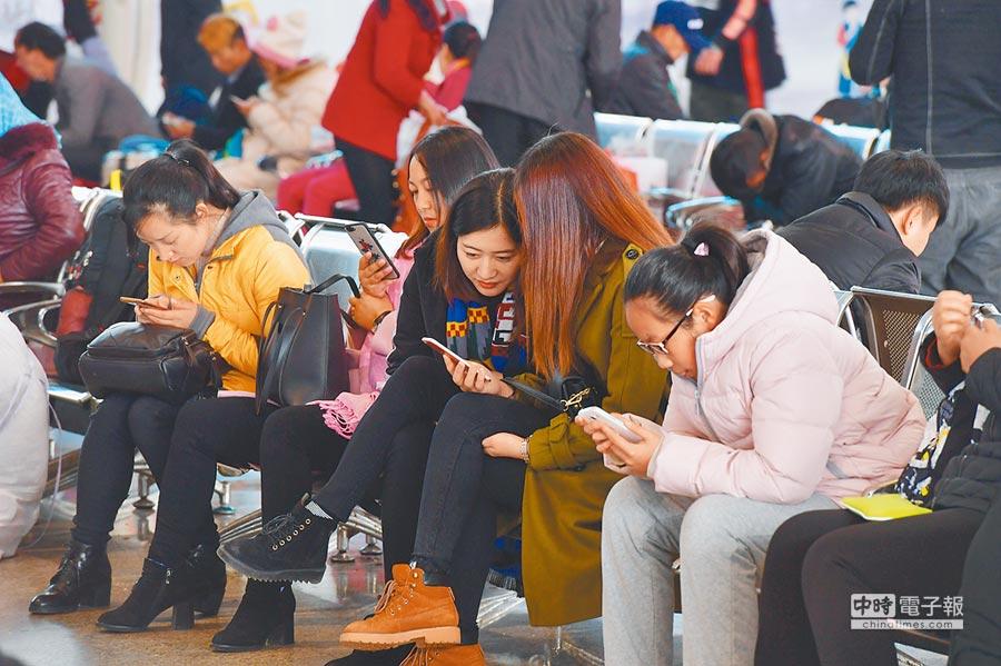 大陸智慧手機市場陷入停滯。圖為2018年2月1日,昆明火車站候車室旅客低頭玩手機。(中新社)