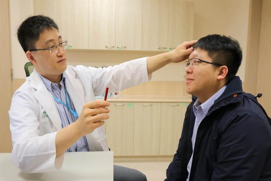 亞大醫院神經內科主任王馨範(左),為患者(非當事人)測試動作協調能力。(林欣儀攝)