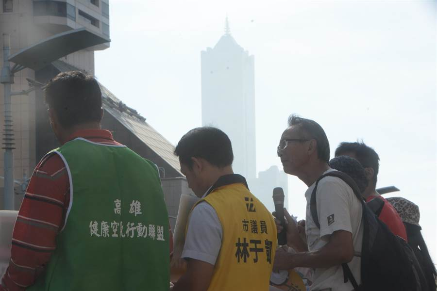 環保團體抗議時,遠方的高雄地標85大樓隱身在霧霾中,顯見空氣品質確實不佳。(林宏聰攝)