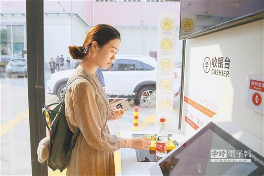 民眾在上海街頭「無人超市」便利商店內自助掃碼付款。(新華社資料照片)