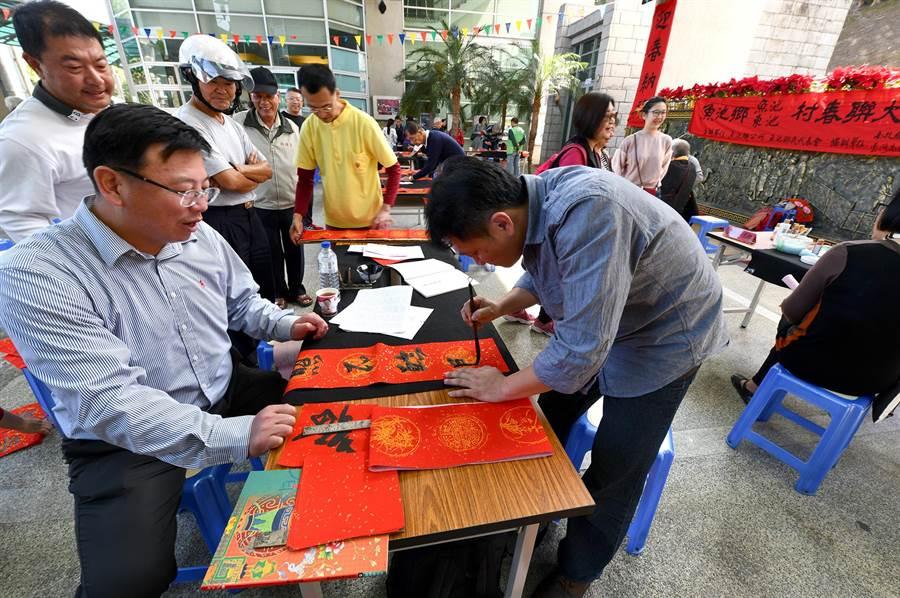 魚池鄉長劉啟帆(左前)在「金豬報喜迎新春」活動中,與書法家互動。(沈揮勝攝)