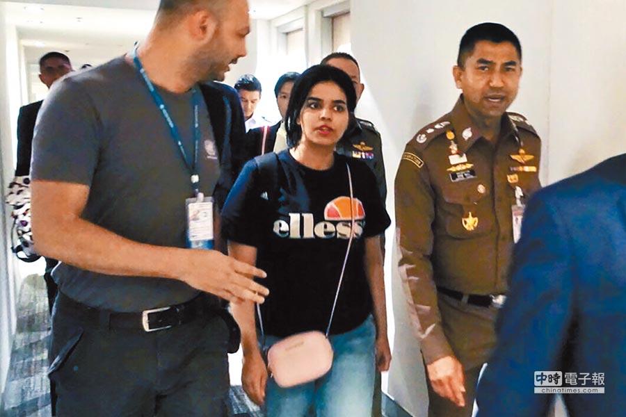沙烏地少女拉哈芙.奎農(中)本月7日在泰國移民局官員(右)陪同下,與聯合國難民署官員(左)會面。(法新社)