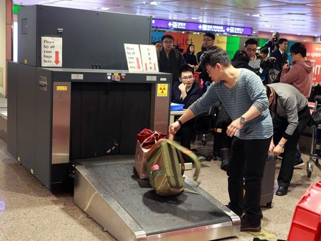 關務署台北關15日試辦提升高風險地區入境旅客手提行李抽檢比例為防疫把關,雖然立馬查獲夾帶豬肉丸子,但造成入境旅客在綠線檯前大排長龍的等待檢查。(陳麒全攝)