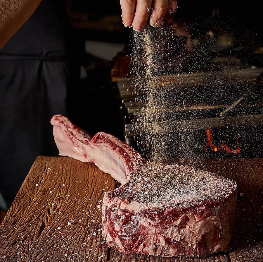 直接用炭火燒烤的〈戰斧牛排〉,會先灑上鹽巴與辛香料提味。(圖/晶華酒店)