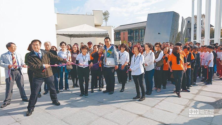 台南市長黃偉哲(左二)與民眾一起拉繩牽引已故雕塑家楊英風作品。(程炳璋攝)
