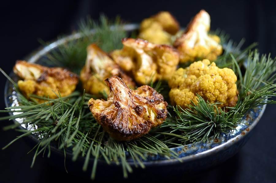 〈黃花椰菜-綠莎莎醬-蓓夏美-起士〉的黃花椰菜以奶油半煎炸至上色,然後放置在墊著松葉的盤中,而帶有煙燻香與淡淡松葉香。(圖/姚舜)