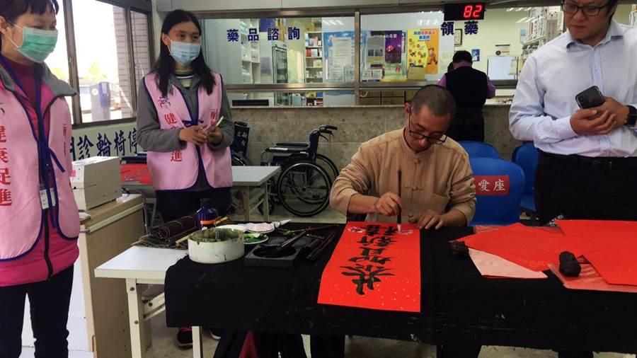 恆春旅遊醫院18日聘請書法家王泰老師到院內現場揮毫,贈送喜氣洋洋的春聯給民眾。(謝佳潾攝)