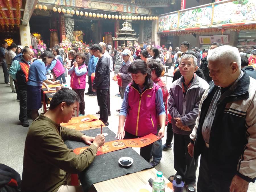 大里福興宮舉辦寫春聯活動,吸引許多民眾排隊索取。(林欣儀攝)