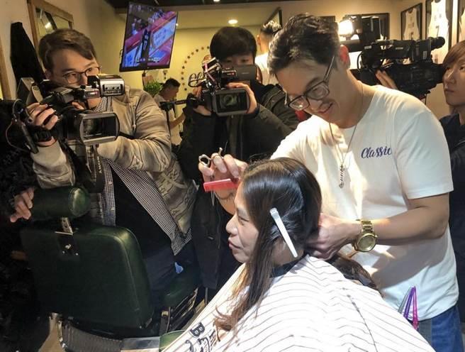 謝玉娟讓自己愛徒李奇勳修剪頭髮。(黃及人攝)