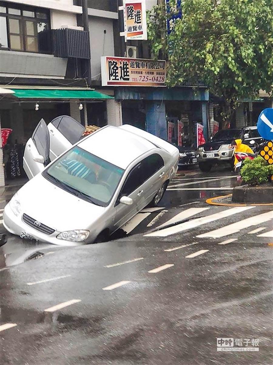 去年8月底高雄連日豪大雨,高市一心、和平路口出現超大天坑,汽車活生生被吞進洞裡,所幸駕駛自行逃脫無礙。(本報資料照片)