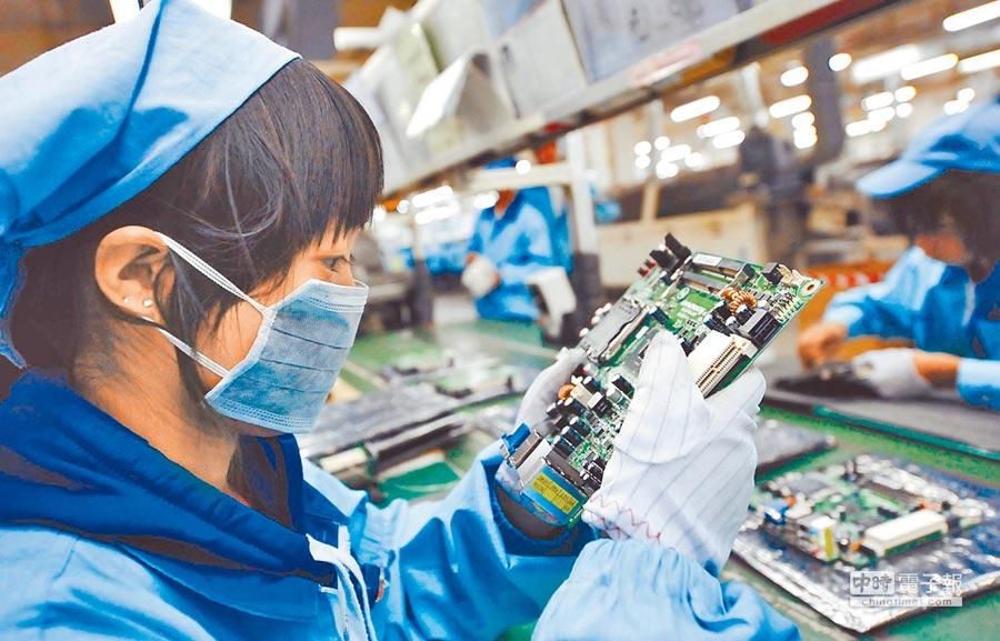 台企對大陸投資,以電子產業居大宗。圖為一位女工在檢查電腦主板產品。(新華社資料照片)