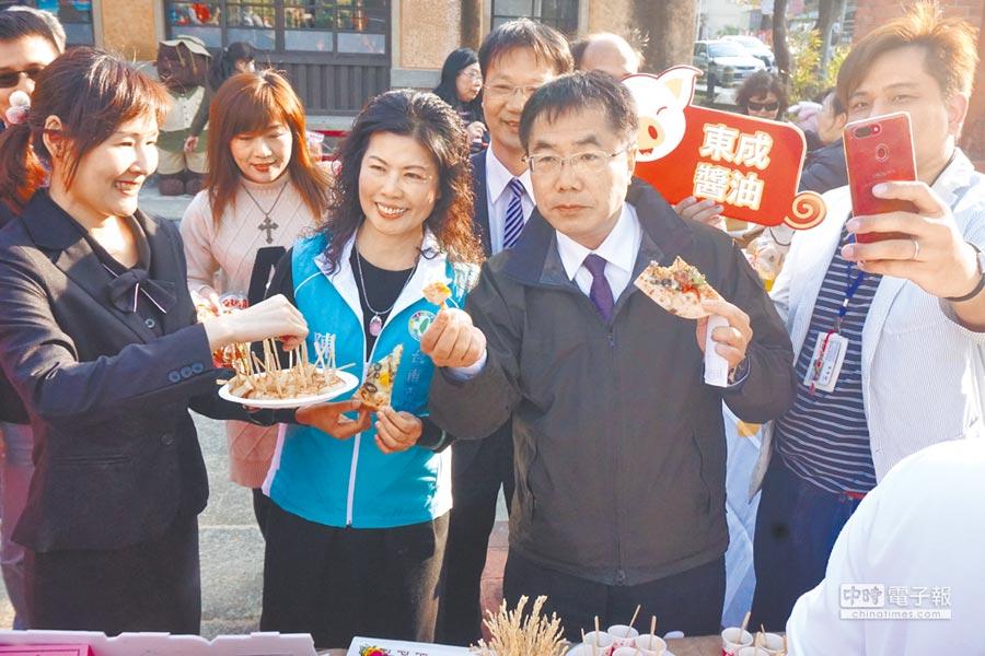 台南市府22日下午舉行新化年貨大街宣傳記者會,台南市長黃偉哲(前排右二)、市議員陳碧玉(前排右三)現場試吃披薩和蘿蔔糕等新化美食,讚不絕口。(李其樺攝)