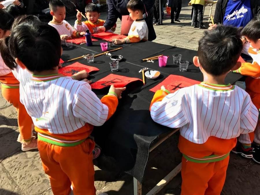 北埔鄉公所24日在慈天宮前舉辦春節揮毫活動,除了邀請名家贈春聯,還有逾200名學童參與,場面很「福趣」。(莊旻靜攝)