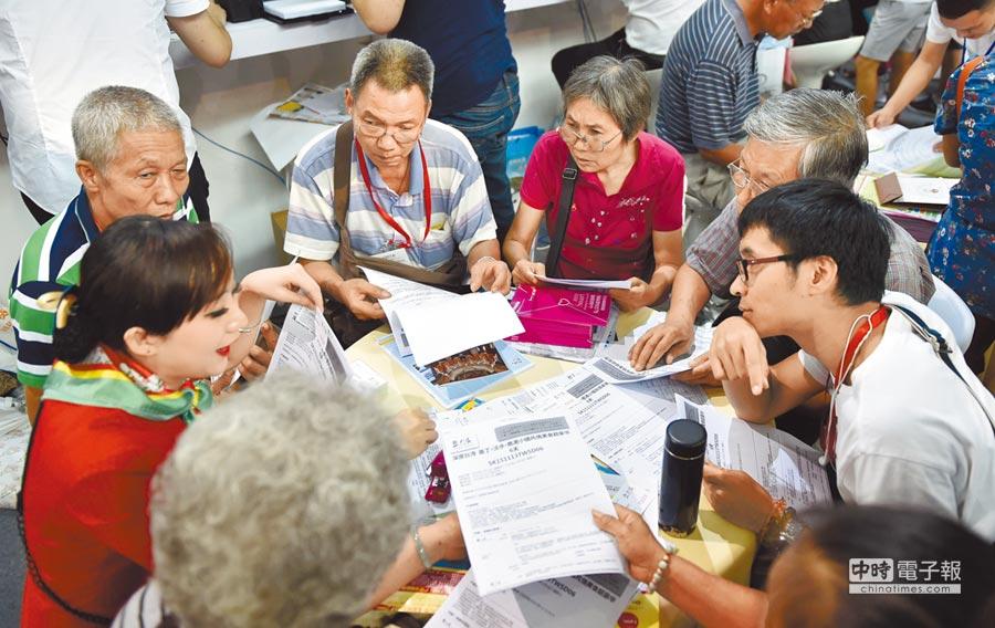 大陸父母出遊子女買單,「銀髮旅遊」市場潛力大。圖為廣州一位旅行社人員在為老人們介紹台灣遊產品。(新華社)