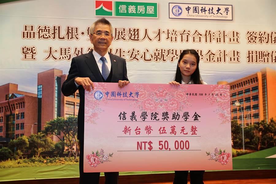 信義企業集團董事長周俊吉(左),25日頒發獎學金給中國科大學生。(徐養齡攝)
