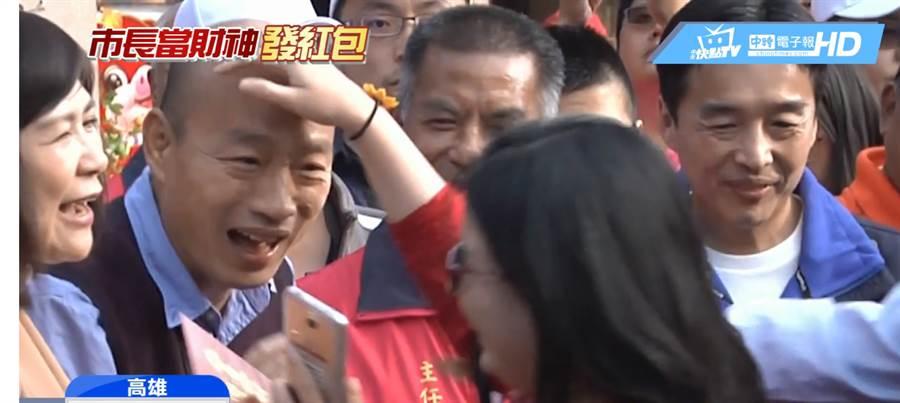 韓國瑜發紅包時,遭女韓粉摸頭。(圖/翻攝自中天新聞YouTube)