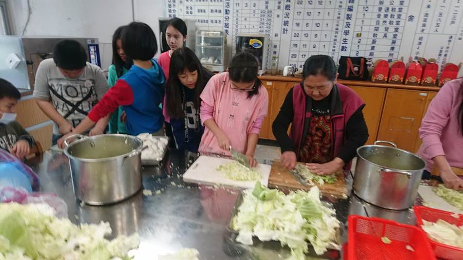 校內高關懷家庭的小朋友們採摘農場內的芹菜、蔥和高麗菜後親手包水餃。(校方提供)
