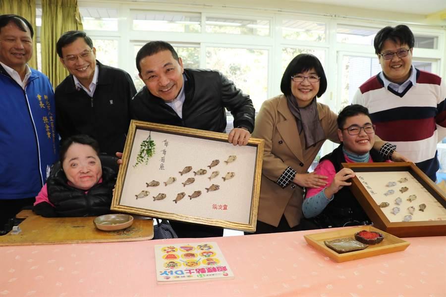 新北市長侯友宜與八里愛心教養院院生合力完成年年有餘的畫作。(吳岳修攝)