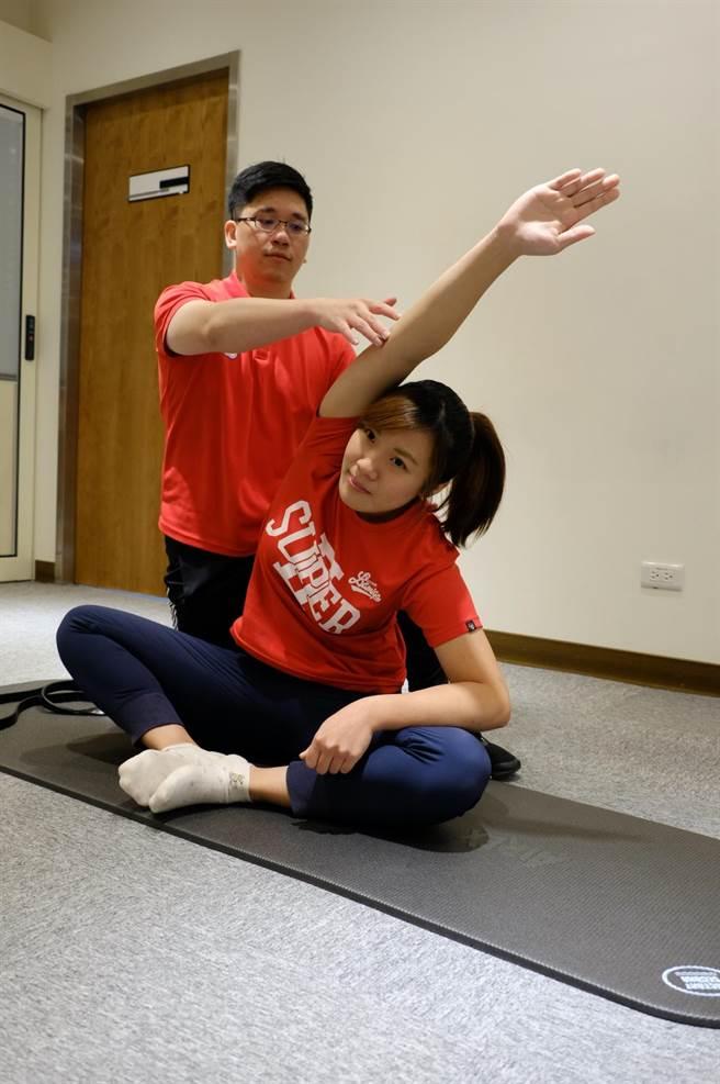 側腰伸展,此動作會伸展側腰經常痠痛的肌肉,需雙腳盤腿,將右手往左邊膝蓋延伸,延伸至有被拉長的感覺,約20秒後換邊。(壢新醫院提供)