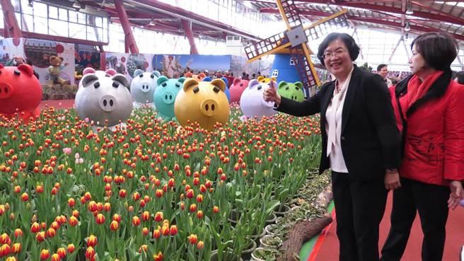 王惠美忍不住在美麗的花卉藝術裝置前留影。(鐘武達攝)