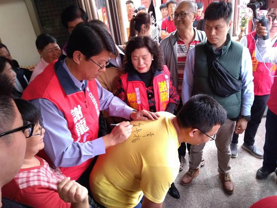 謝龍介日前到玉井北極殿拜票,熱情粉絲衝向前請謝龍介在背上簽名。(劉秀芬攝)