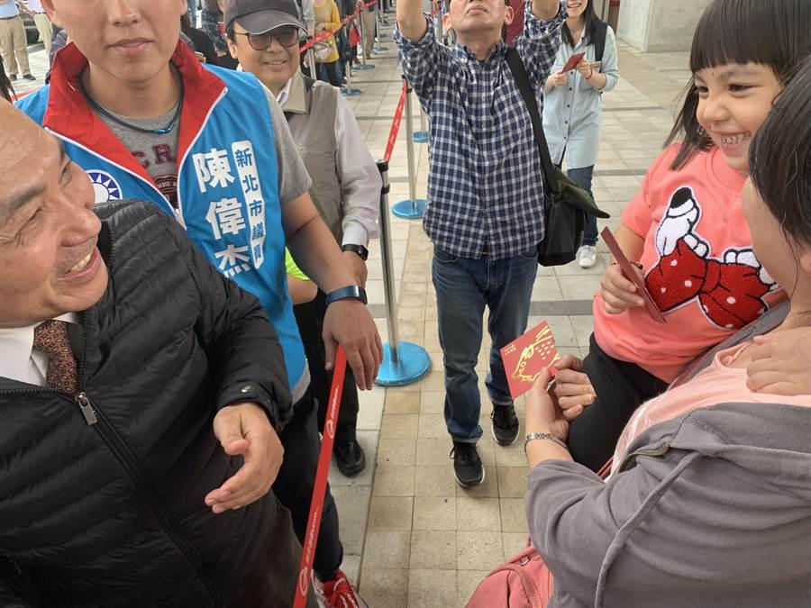 新北市長侯友宜發紅包給等候淡海輕軌的旅客。(王揚傑攝)