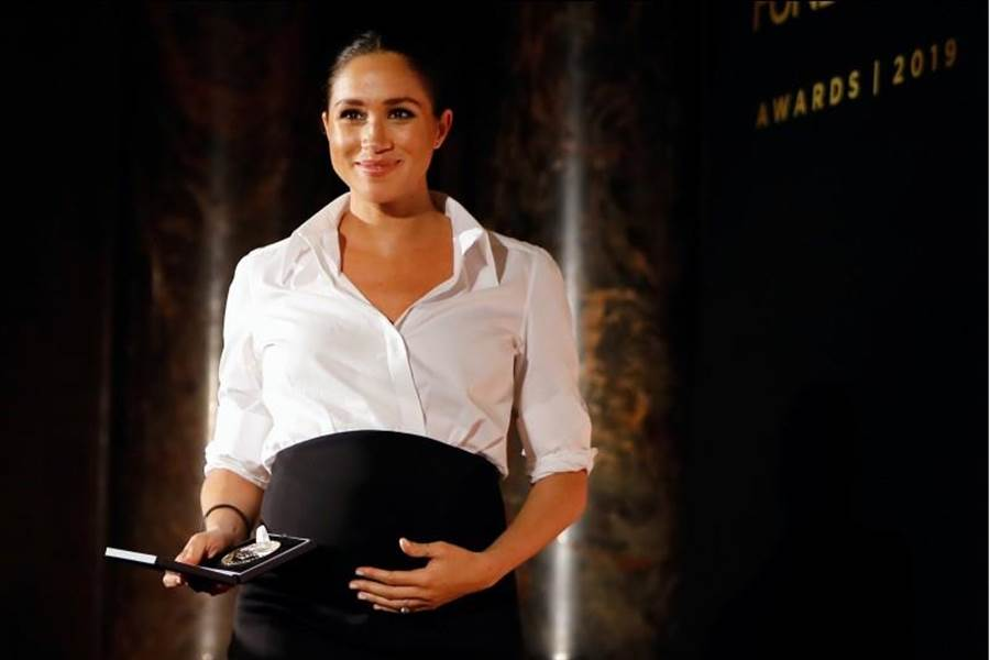 梅根2月7日挺著孕肚,在倫敦出席「表揚卓越獎」(Celebrating Excellence Award)頒獎典禮,並頒發獎項的神情。(路透)
