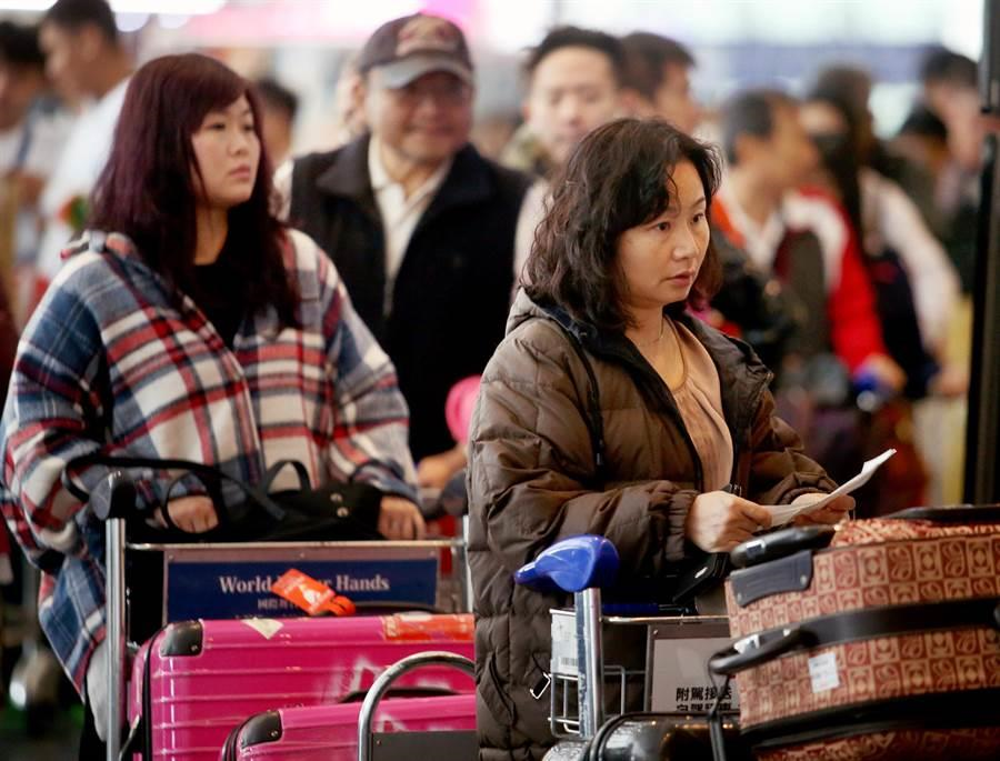 搭乘華航班機的旅客,正在桃園機場內排隊報到。(范揚光攝)